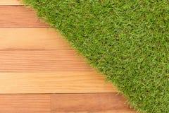 Syntetyczna zielona trawa i drewniana ściana, naturalny tło Zdjęcie Stock