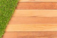 Syntetyczna zielona trawa i drewniana ściana, naturalny tło Obrazy Stock