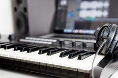 Syntetyka hełmofonu i klawiatury lying on the beach na Muzycznym studiu Zdjęcie Stock