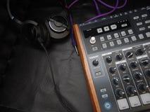Synthétiseur avec des écouteurs sur le fond en cuir noir avec le câble pourpre de correction Images stock