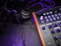 Synthétiseur avec des écouteurs sur le fond en cuir noir avec le câble pourpre de correction Photo libre de droits