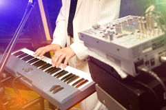 Synthesizer. The musician plays on synthesizer, hands in the staff, multi-coloured light Royalty Free Stock Photo