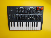 Synthesizer auf gelbem Hintergrund mit orange Flecken verkabelt Stockbilder
