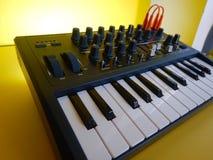 Synthesizer auf gelbem Hintergrund mit orange Flecken verkabelt Lizenzfreie Stockfotografie