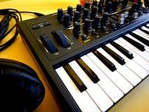 Synthesizer auf gelbem Hintergrund mit orange Fleckenkabeln und -kopfhörern Lizenzfreies Stockfoto