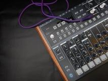Synthesizer auf schwarzem ledernem Hintergrund mit purpurrotem Fleckenkabel Stockfotos