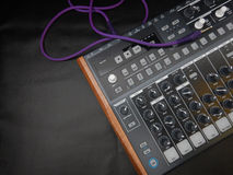 Synthesizer on black leather background with purple patch cable Stock Photos