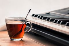 Synthesizer and cup of tea on a wooden surface. stock image