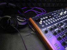 Synthesizer with headphones on black background with purple patch cable Stock Photo