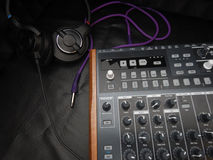 Synthesizer with headphones on black leather background with purple patch cable Royalty Free Stock Photo