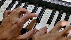 Synthesizer het spelen de hand van de mensenpiano over sleutels in werking die wordt gesteld die stock video