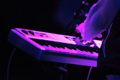 Synthesizer keyboard. Rock concert series: synthesizer keyboard and musician's arm, lit by purple and blue Royalty Free Stock Photography