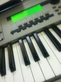Synthesizer keyboard music instrument and green LCD screen royalty free stock photo