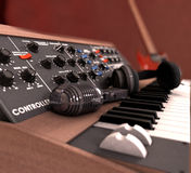 Synthesizer. Microphone and headphones lay on a synthesizer. In the background blurred guitar Stock Photo