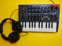 Synthesizer on yellow background with orange patch cables and headphones Royalty Free Stock Photo