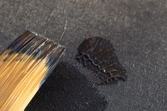 Synthetic brush with black paint close-up. Black paint. Draw with black paint. Black slate. Paint for decoration. The effect of the slate. Interior decoration Royalty Free Stock Image