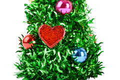 Synthetic Christmas tree with colored balls and heart on branche. Christmas tree with decorations and heart isolated on white background, green and bright Stock Photos