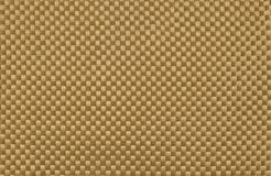 Synthetic kevlar fiber cloth. Background of light and strong gold kevlar fiber cloth used in personal armor, racing boat and other sport equipment construction Stock Photo