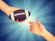 Synthetic rugby ball. In hand. Abstract blue backround. Light with stripes royalty free stock images