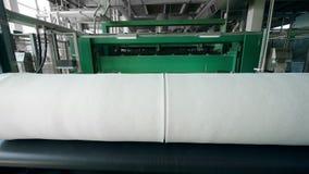 Synthetisch die materiaal in spoelen op een fabriekstransportband wordt gerold stock video