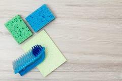 Synthetische sponsen, microfiber servet en borstel voor het schoonmaken op houten raad stock afbeeldingen