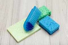 Synthetische sponsen, microfiber servet en borstel voor het schoonmaken op houten raad stock afbeelding