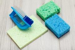 Synthetische sponsen, microfiber servet en borstel voor het schoonmaken op houten raad stock fotografie