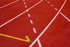Synthetischer Gummi der roten Laufbahn auf dem athletischen Stadion Lizenzfreie Stockfotos