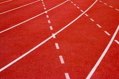 Synthetischer Gummi der roten Laufbahn auf dem athletischen Stadion Lizenzfreie Stockfotografie