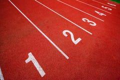 Synthetischer Gummi der roten Laufbahn auf dem athletischen Stadion Lizenzfreies Stockbild