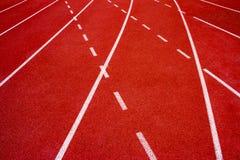 Synthetischer Gummi der roten Laufbahn auf dem athletischen Stadion Stockfotos