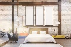 Sypialni wnętrze z biel ścianami i trzy wąskimi pionowo plakatami na one Obrazy Stock