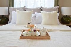 Sypialni wnętrze z dekoracyjną herbatą ustawiającą i deserem na łóżku zdjęcia royalty free