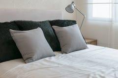 Sypialnia wewnętrzny projekt z popielatymi poduszkami na białym łóżku i dekoracyjnej stołowej lampie Obrazy Stock