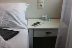 Sypialnia widoku szczegóły z łóżkiem, strona stół z smartphone i kosmetyki na nim, Zdjęcie Stock