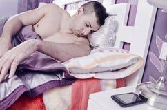 Sypialny młody człowiek blisko smartphone Obrazy Royalty Free