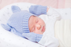 Sypialny mały dziecko jest ubranym trykotowego błękitnego kapelusz z ucho Obrazy Stock