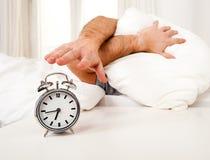 Sypialny mężczyzna zakłócający budzika wczesnym mornin Obrazy Stock