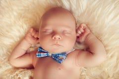 Sypialny nowonarodzony dziecka lying on the beach z łęku krawatem na białym futerku w h Zdjęcie Royalty Free