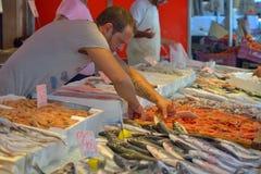SYRACUSE, ITALIE - AOÛT 2015 : Poissonnier vendant les poissons fraîchement pêchés sur un vieux marché local du centre de la vill Photos stock