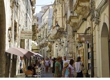 People walking in narrow alley in Syracuse on Ortigia island, Sicily, Italy royalty free stock photo