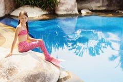 Syrenki dziewczyna z różowym ogonem na skale przy poolside Zdjęcie Stock