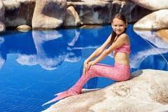 Syrenki dziewczyna z różowym ogonem na skale przy poolside Obraz Stock