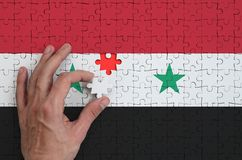 Syria flag is depicted on a puzzle, which the man`s hand completes to fold.  stock illustration