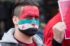 Syria protest face paint. A refugee with Syrian flag face paint protests during the May Day parade in Oslo, Norway, May 1, 2016 Royalty Free Stock Image