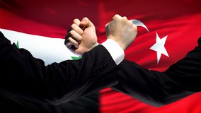 Syria vs Turkey confrontation, countries disagreement, fists on flag background. Stock photo royalty free stock photography