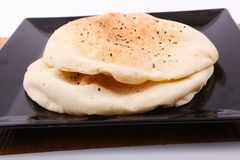 Syrian bread. On black dish on wooden table over white background stock images