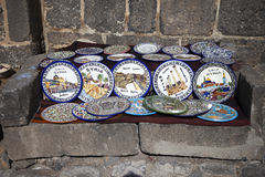 Syrian ceramic plates. Touristic ceramic plates in Bosra on a grey stone divan Royalty Free Stock Photography