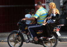 A Syrian family on motorbike. A Syrian family moving all togehter on a motorbike stock photo