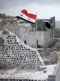 Syrian flag on the walls of the castle Marqab is fluttering in the wind Stock Images